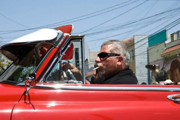 A proud owner of a vintage convertible shows his car at the annual Mission District Carnival