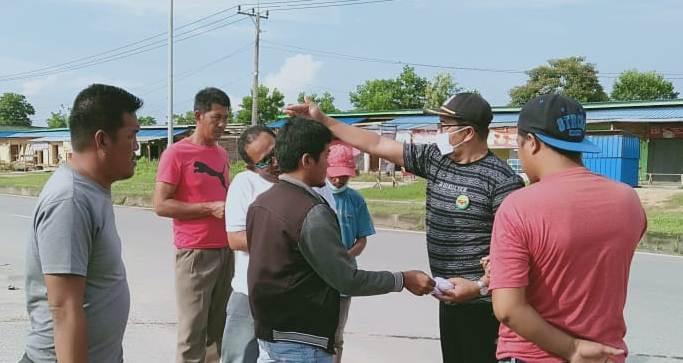 Ketgam: Sekretaris DPD LAT Konsel, Nasran saat membagikan masker kepada pengguna jalan.