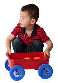 Young boy plays with red wagon