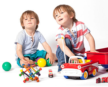 Twin brothers playing with toys