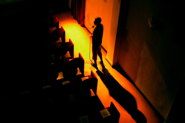 An actor walks alone in an empty theatre.