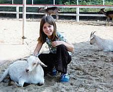 Kama as child petting goat