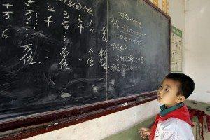 Recurso de archivo. Un niño chino en la pizarra, estudiando matemáticas