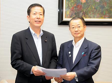 河村官房長官(右)に申込書を渡す公明党の山口政調会長