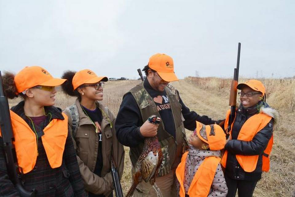 Sommari Muwwakkil celebrated with his daughters Eshante (from left), Inkera, Sommyia and Mikhia after shooting a pheasant last weekend at the Harding Gamebirds hunting preserve in northern Missouri. They participated in a hunt organized by the Black Wolf Hunting Club to introduce more African-Americans to hunting.