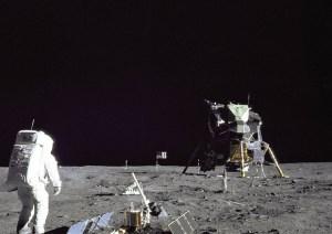 Buzz Aldrin sul suolo lunare, vicino a materiali per gli esperimenti e sullo sfondo il modulo dell'allunaggio