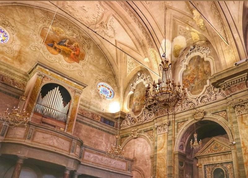 Angolo interno della Collegiata di San Michele Arcangelo. In foto, un organo, pareti finemente decorate e numerosi lampadari.