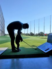 Stefen teaching Blake how to golf at Top Golf