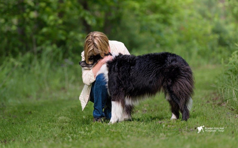 Person hugging Border Collie with face hidden in fur