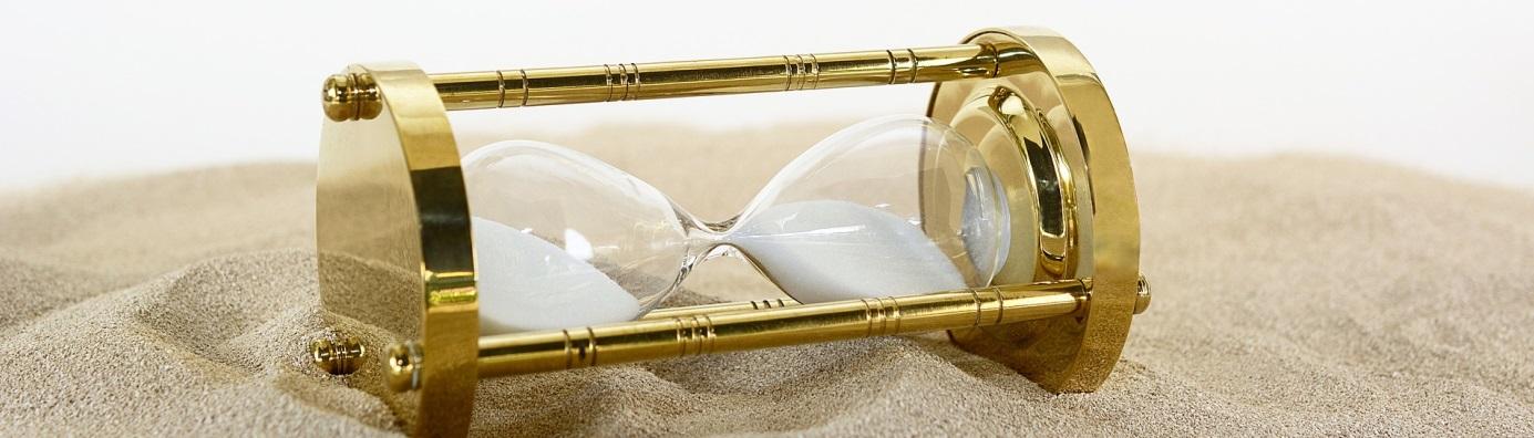 Image décorative : sablier doré couché sur du sable blanc