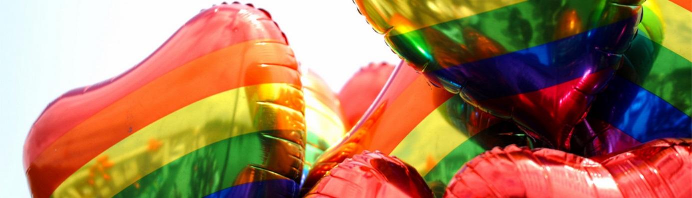 Image décorative : ballons en forme de coeurs aux couleurs du drapeau LGBT+.
