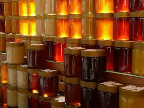 Photographie montrant une rangée de pots de miel empilés, éclairé par une lumière qui vient de derrière eux et fait ressortir les différentes teintes.