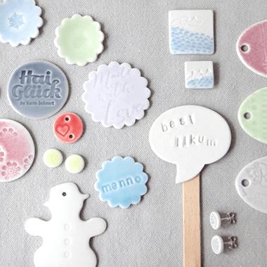 viele verschiedene Schmuckstuecke aus Porzellan, die im Schmuckworkshop entstanden sind: Ohrstecker, Broschen, Anhaenger