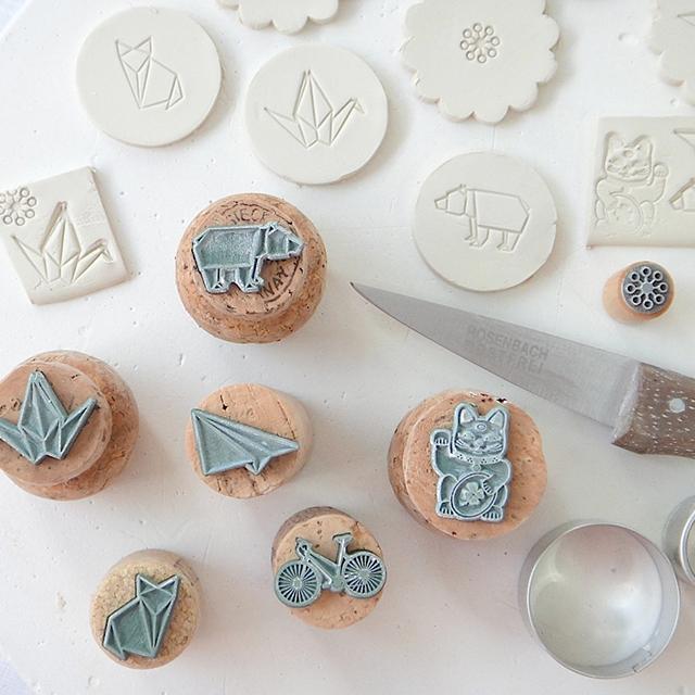 Stempel und rohe, gestempelte Porzellanplaettchen, daneben ein Porzellanmesser