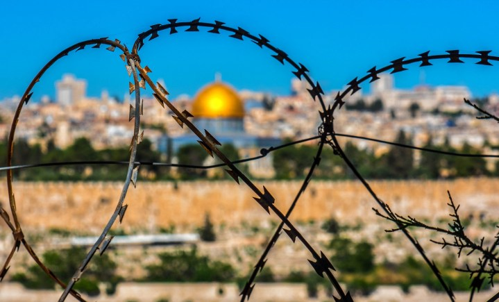 A view of the Dome in Jerusalem viewed through a barbed wire fence.