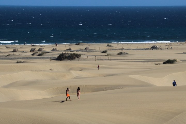 A view of the sea from the sand dunes. A couple are taking photos of each other in the foreground.