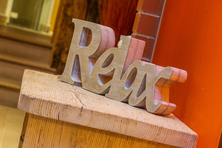 A wooden sign spelling out th word, relax.