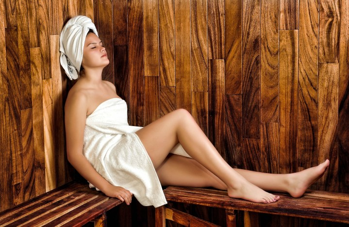 A lady in a white towel relaxing inside a sauna. Nudity is Austrain saunas is compulsory.