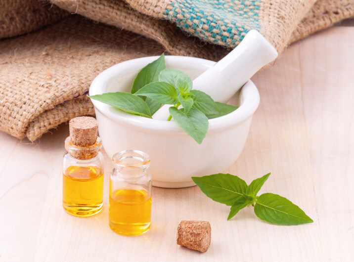 Öl, Mörser und Stößel mit Heilpflanzen