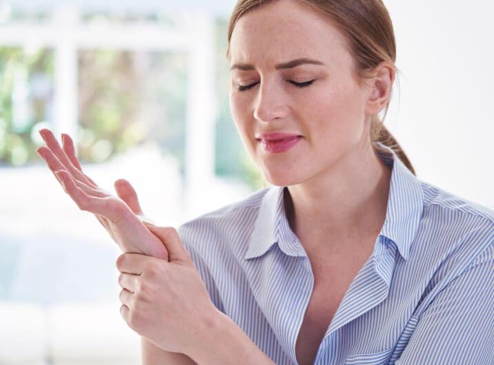 Frau hält sich Handgelenk wegen Schmerzen