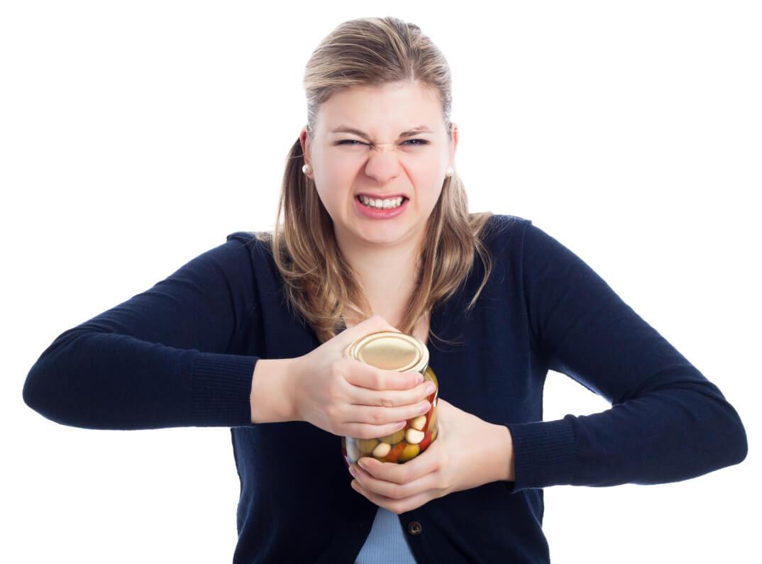 Frau versucht verkrampft Glas zu öffnen