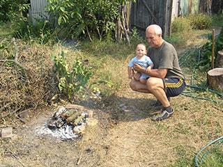 Лука с дедом Сашей следят за костром для шашлыков