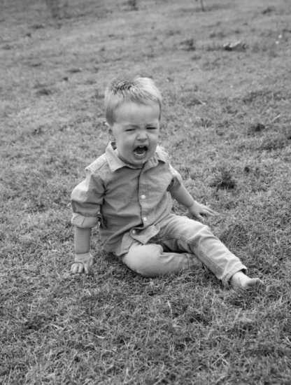 Little boy having tantrum in the grass black and white