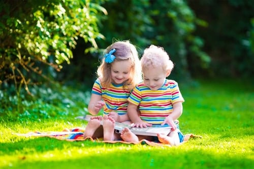 Two girls looking at a picture book.