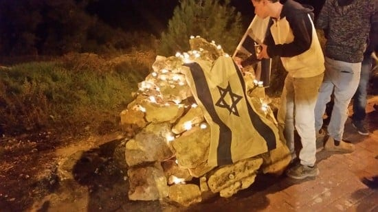 A student leaves a candle at the site of the murder of Rav Yaakov Don.