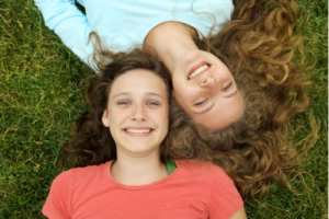 Two young girls lying on the grass in opposite directions, smiling best friends