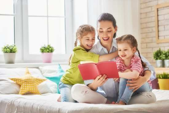 Mother reads to two laughing girls