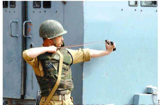 A CRPF personnel using slingshot during protests - Photo by: Bilal Bahadur