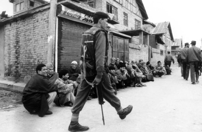An Indian soldier walks past Kashmiris during a crackdown in Srinagar