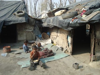 Kids sitting outside a  makeshift house in a slum