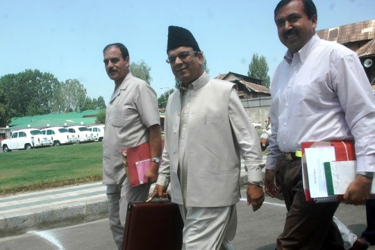 Finance minister Abdul Rahim Rather outside state assembly complex with budget documents.