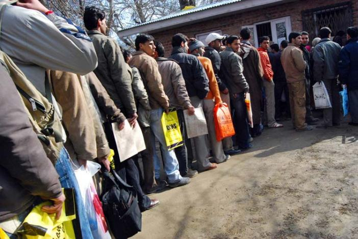 Youth standing in queue outside PSC Srinagar with admission forms in their hands. Photo: Bilal Bahadur