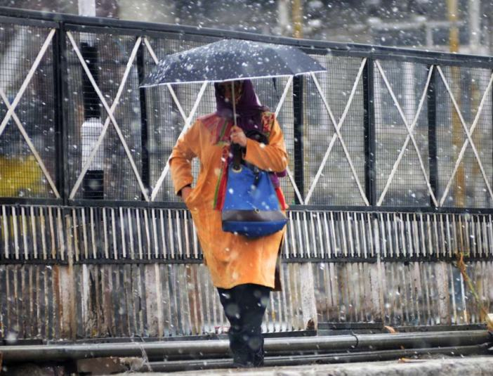 A girl walks in Srinagar as moderate snowfall carpets the city under white.