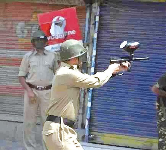 A policeman firing controversial pellet gun towards civilian protesters in Srinagar.