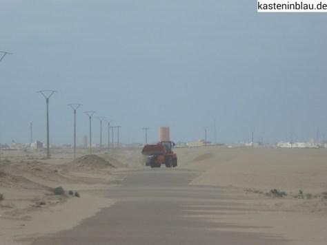 Die Zufahrtsstraße nach Tarfaya wird vom Sand befreit.