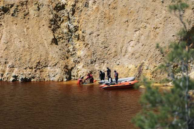 """Divers and forensic officers search Kokkinopezoula lake, also known as """"red lake"""", for possible bodies of victims of a suspected serial killer near the village of Mitsero"""