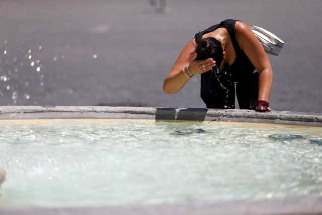 A woman cools off at a fountain in downtown Rome as a heatwave hits.