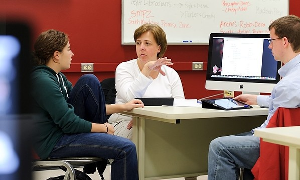 Katy Culver, center, a faculty associate in journalism and mass communication, facilitates an editorial-planning discussion with journalism students in a magazine-production class in Vilas Communication Hall at the University of Wisconsin-Madison on Nov. 3, 2011. The class, which uses a combination of iPad tablets, laptop computers and traditional desktop computers, produces Curb Magazine. (Photo by Jeff Miller/UW-Madison)