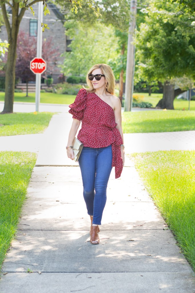 Wearing a polka dot one shoulder puff sleeve belted top with skinny jeans.