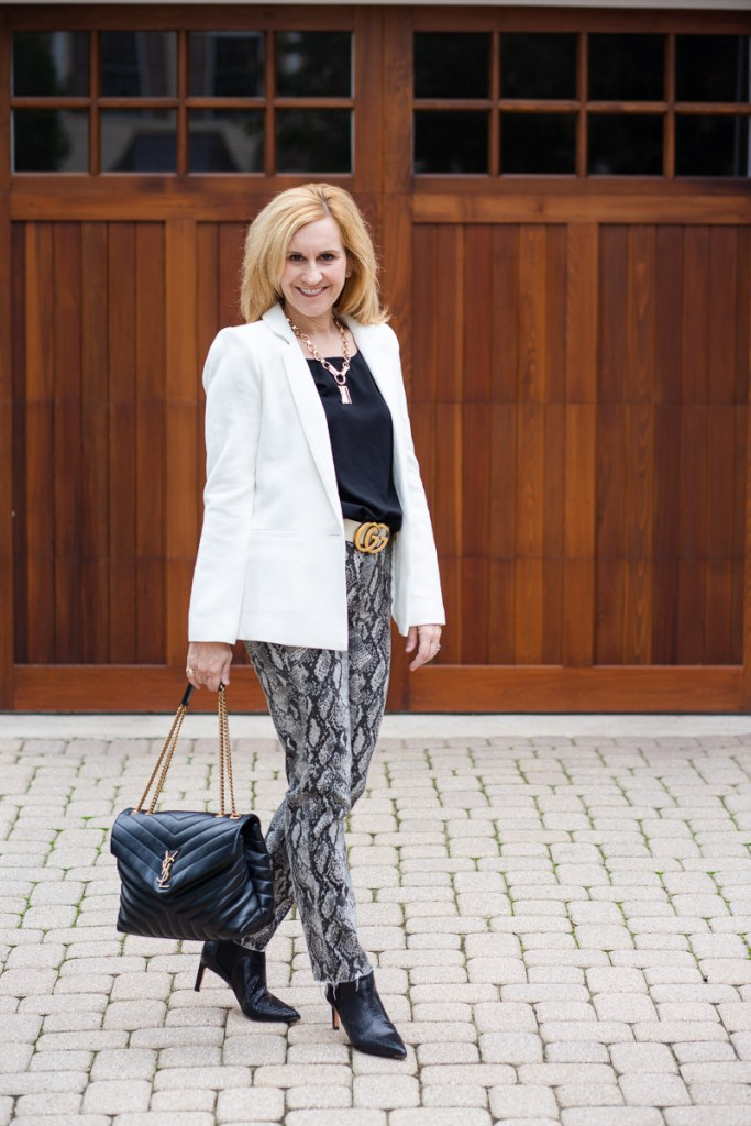 Pairing a white blazer with snakeskin jeans.