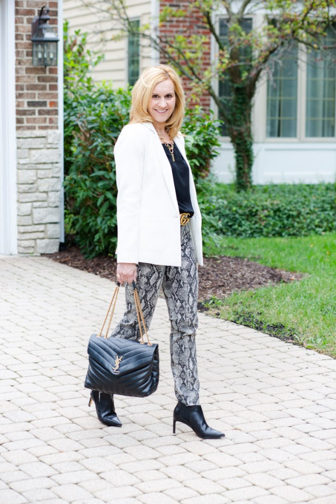 Styling a white blazer with snakeskin jeans and black booties.