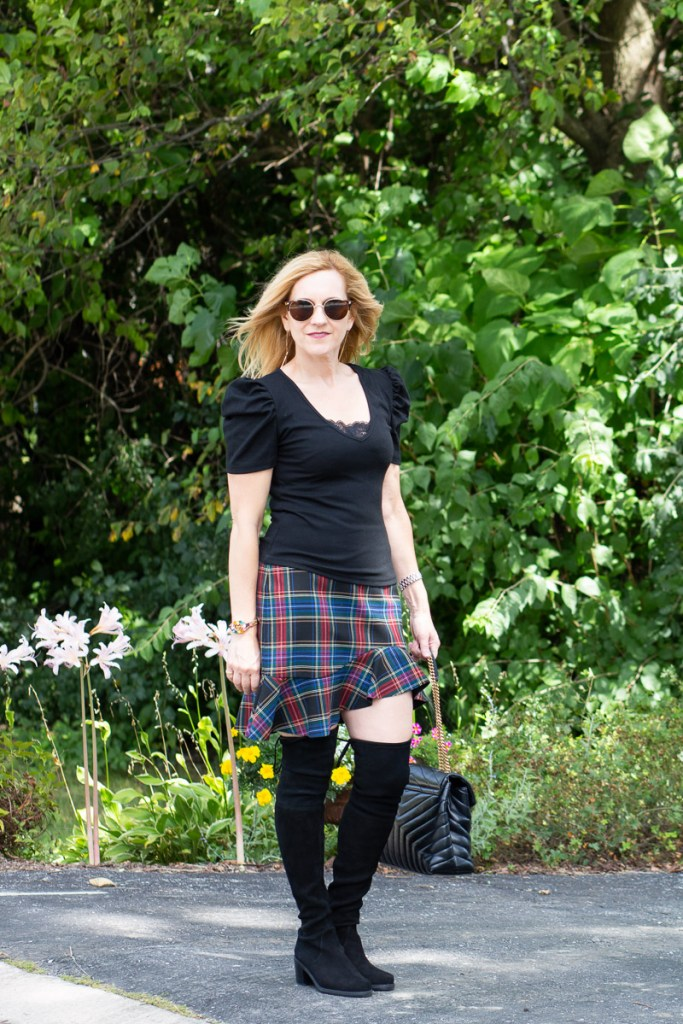 Styling suede over the knee boots with a plaid skirt and black puff sleeve top.