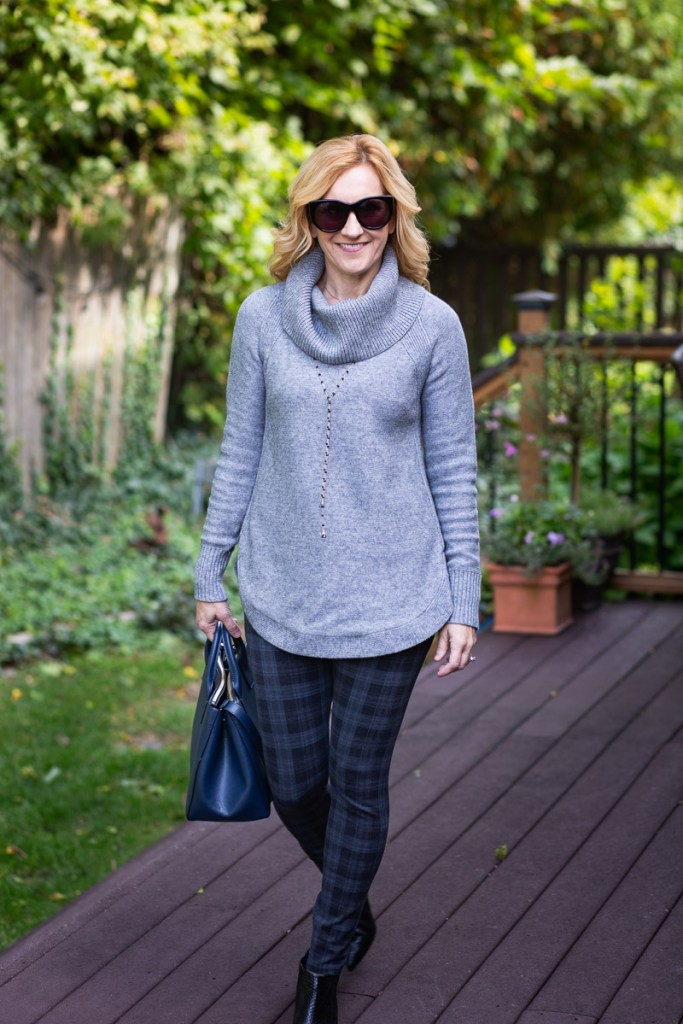 A cozy chic look featuring a grey sweater, plaid leggings, and black booties.