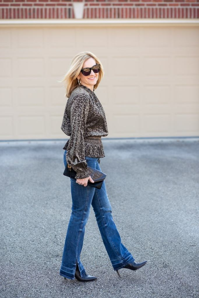 Pairing a long sleeve leopard print blouse with flared jeans.