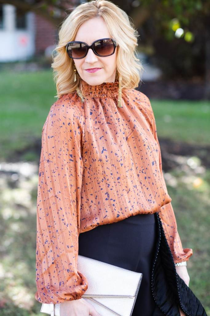 A long sleeved rust-colored bodysuit paired with ruffle pants.