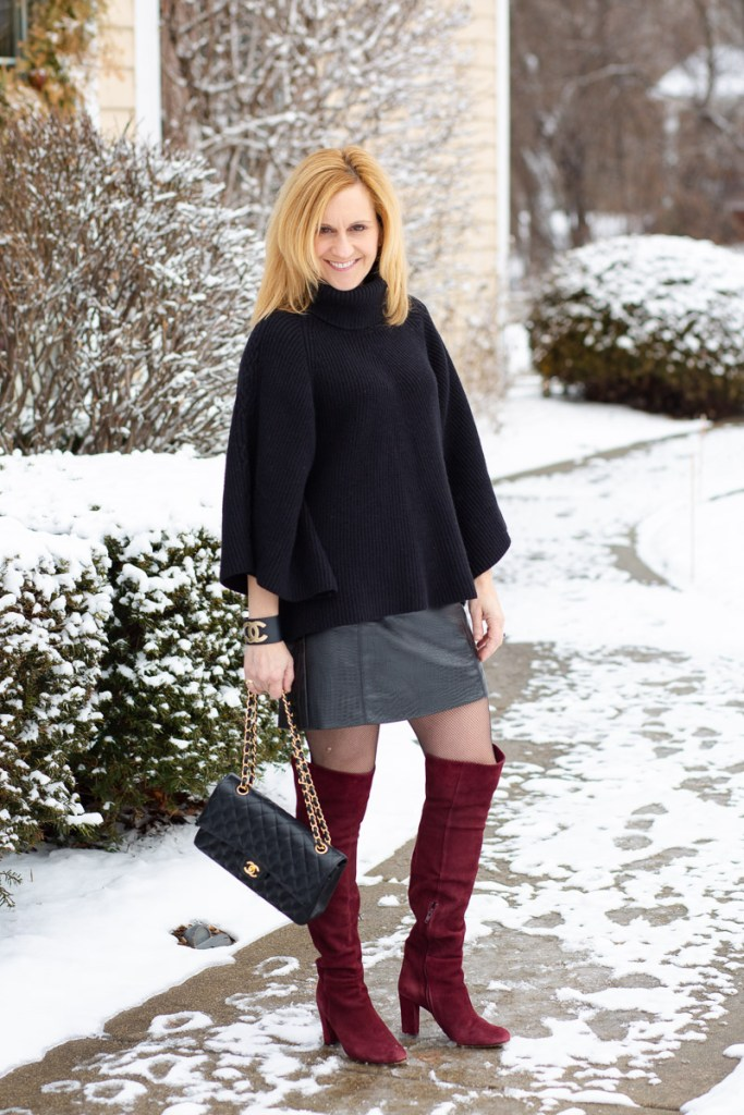 Styling a black sweater with a leather mini skirt and over the knee boots.